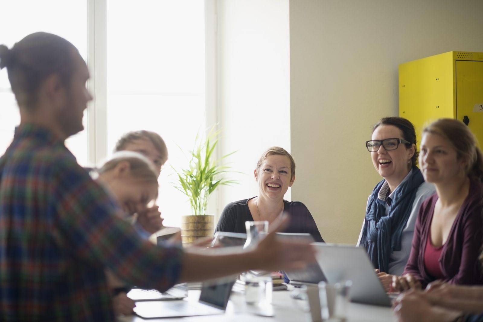 Möte med skrattande deltagare runt ett bord, som tittar på en person som står upp och presenterar. I mitten sitter Malin Valsö, från Elevhälsokonsulterna.