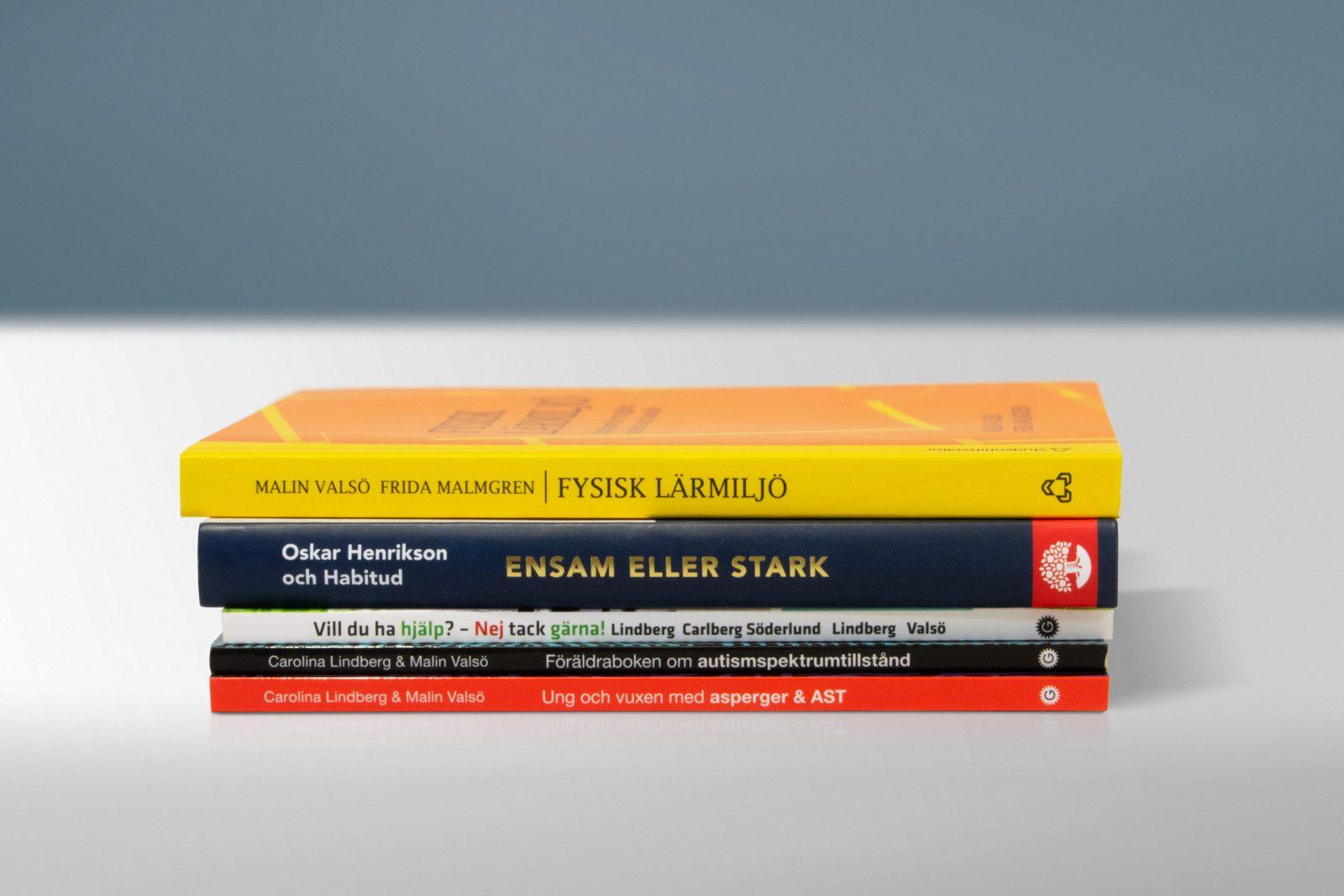 En traver böcker, skrivna av Malin Valsö, ligger på ett bord
