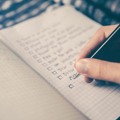checklista på rutigt papper och en hand som håller i en penna